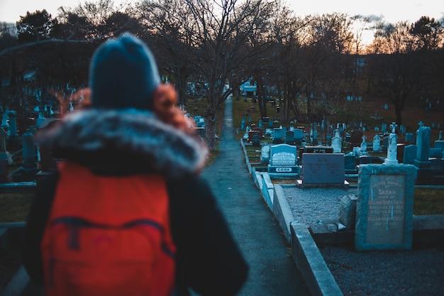 Staande vrouw tegenover een begraafplaats