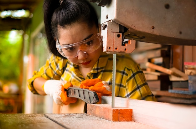 Staande vrouwen zijn ambachtelijk bezig met het snijden van hout op een werkbank met lintzagen elektrisch gereedschap