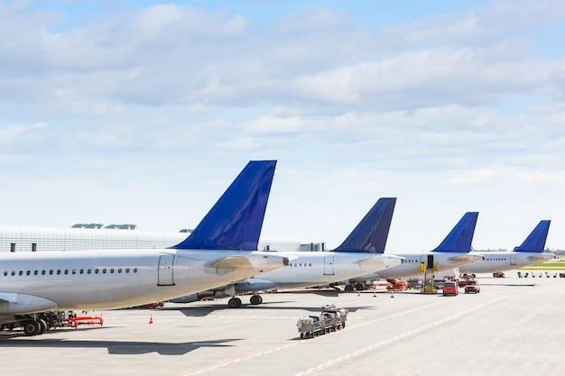 Staarten van sommige vliegtuigen op de luchthaven tijdens het instappen