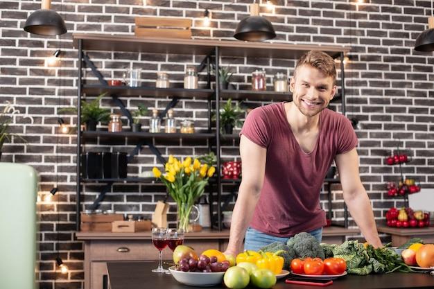 Staat in de keuken. knappe bebaarde vriend die breed glimlacht terwijl hij in de keuken staat voordat hij kookt