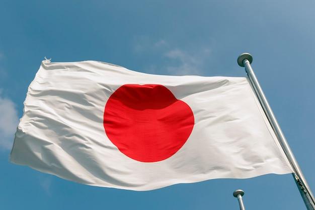 Staat japanse vlag op de sterke wind over blauwe hemelachtergrond