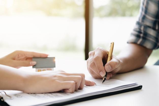Staatsagent geeft pen en documenten overeenkomst met klant om contract te ondertekenen.