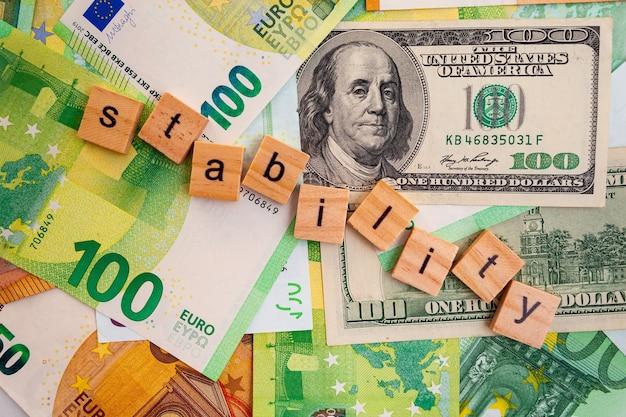 Stabiliteitsinschrijving op houten kubussen op de textuur van amerikaanse dollars en eurobankbiljetten