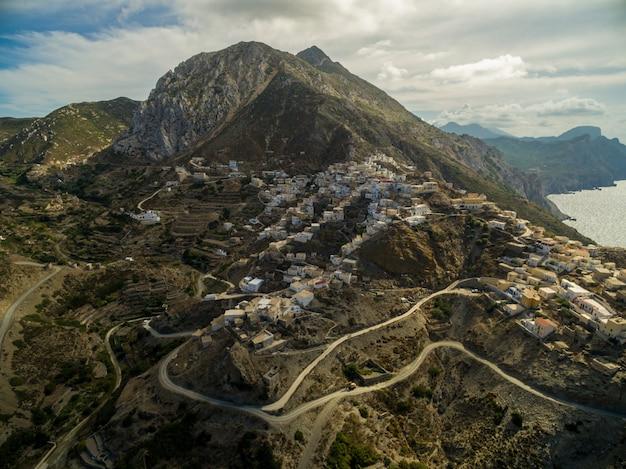 Stad in griekenland met rotsachtige bergen en wegen omgeven door zee