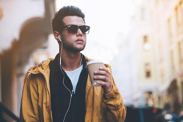 Stad levensstijl. knappe jonge man in koptelefoon met koffiekopje tijdens het wandelen langs de straat van de stad
