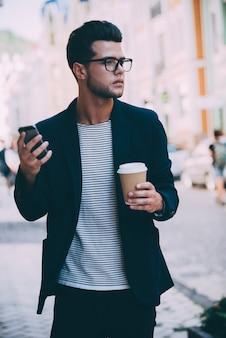 Stad levensstijl. knappe jonge man in slimme vrijetijdskleding die langs de straat loopt terwijl hij een koffiekopje en een smartphone vasthoudt