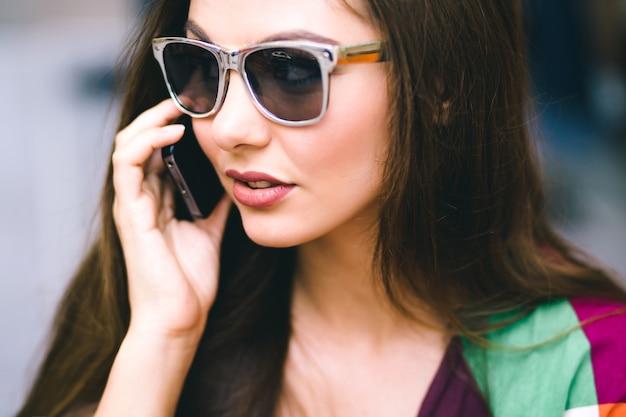 Stad levensstijl portret van mooie brunette vrouw met behulp van slimme telefoon, spreken en glimlachen, lichte kleding, vintage filmkleuren.