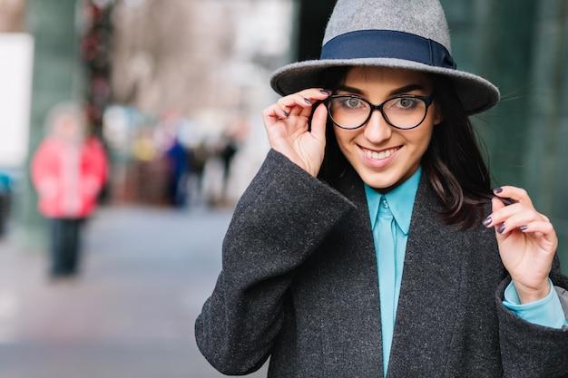 Stad portret stijlvolle charmante jonge vrouw in grijze vacht, hoed lopen op straat. moderne zwarte bril, glimlachen, echte gelukkige emoties uitdrukken, luxe levensstijl, modieus model.