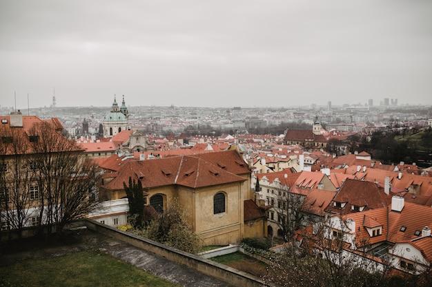 Stad praag met rode daken en kerk in de mist. uitzicht op de stad van de oude stad van praag. rustiek grijze tinten