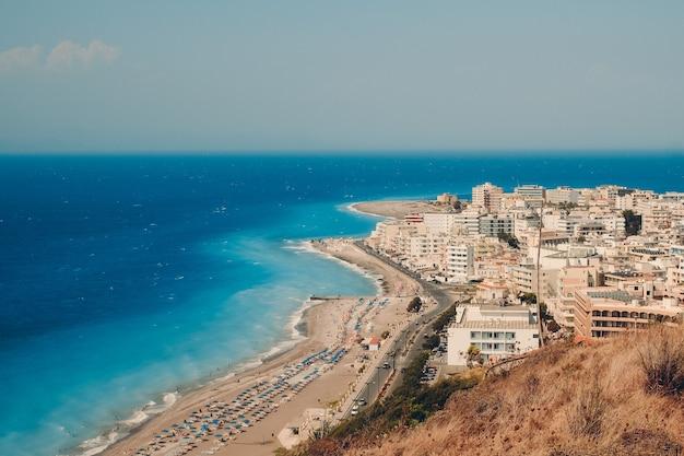 Stad rhodos in griekenland met een diepblauwe zee en een bleke heldere hemel