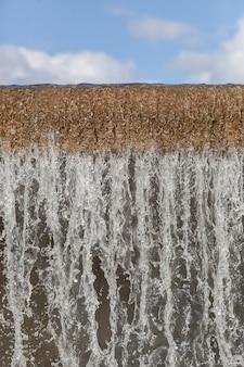 Stad rivier waterval grote cascade muur close-up op een zomerdag, zijaanzicht van de vallende waterstroom en water schuim aan de onderkant