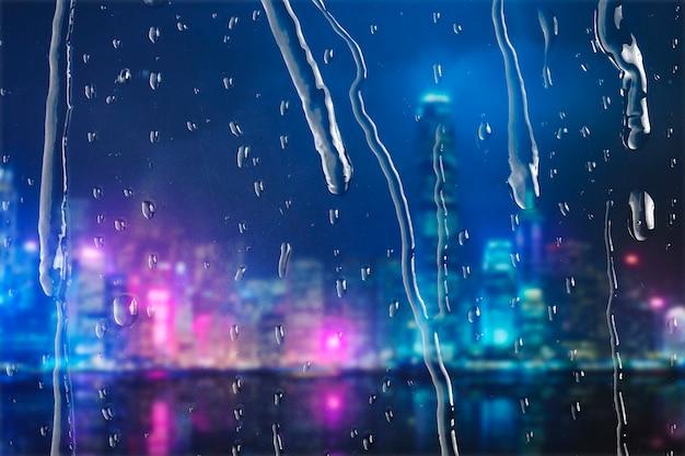 Stad 's nachts door raam met regendruppels