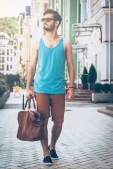 Stad verkennen. volledige lengte van een knappe jongeman in een draagtas met vrijetijdskleding en wegkijkend terwijl hij over straat loopt