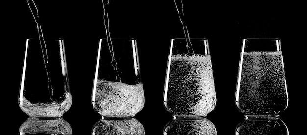 Stadia van het gieten van water in een glazen beker op zwarte achtergrond