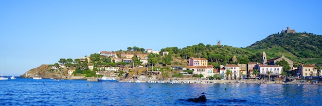 Stadje op een heuvel met een strand en een kerk in een middeleeuwse haven met boten en mensen. reis concept
