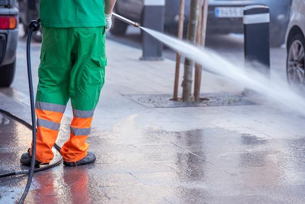 Stadsarbeider met een waterdrukpistool. reiniging van straten en straatmeubilair tijdens epidemie