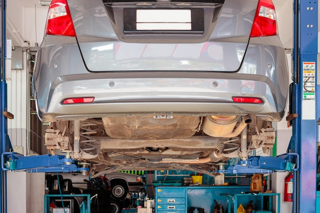 Stadsauto in het opheffende materiaal in de garage die reparatie en fix zijn, concept auto het bevestigen.