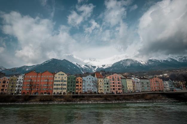 Stadscentrum van innsbruck met kleurrijke huizen langs de rivier de inn en de oostenrijkse berg, oostenrijk