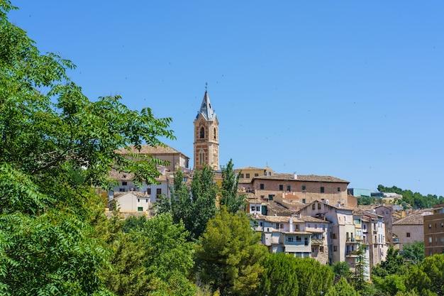 Stadsgezicht met een klokkentoren omgeven door zwaluwen op een zonnige zomerdag