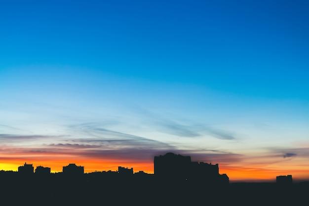 Stadsgezicht met prachtige varicolored levendige dageraad. verbazingwekkende dramatische blauwe hemel met paarse en violette wolken boven donkere silhouetten van stadsgebouwen