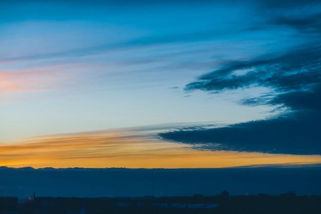Stadsgezicht met prachtige varicolored levendige dageraad. verbazingwekkende dramatische blauwe wolkenhemel boven donkere silhouetten van stad die daken bouwen. atmosferische achtergrond van oranje zonsopgang bij bewolkt weer. kopieer ruimte