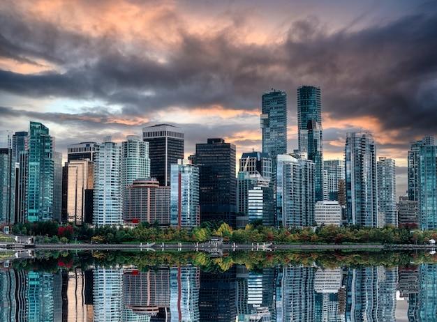 Stadsgezicht van drukke glanzende zakelijke gebouwen reflectie op het water in de avond in stanley park