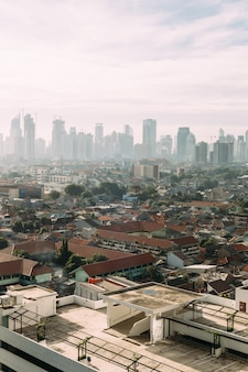 Stadsgezicht van jakarta met hoogbouw, wolkenkrabbers en lokale dakgebouwen met rode dakpannen