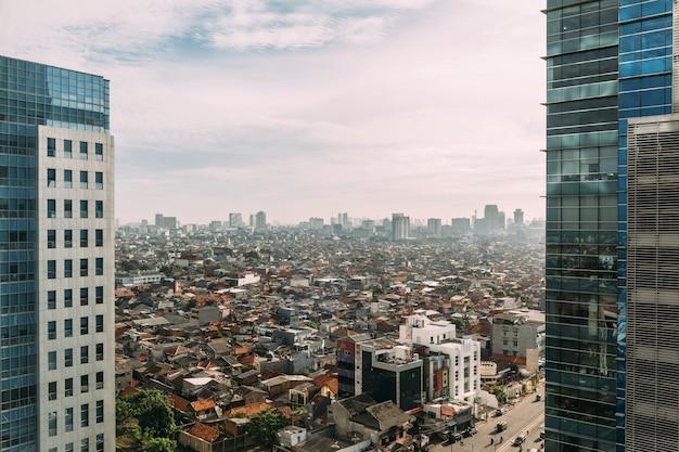 Stadsgezicht van jakarta met hoogbouw, wolkenkrabbers en lokale dakgebouwen met rode dakpannen.