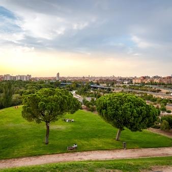 Stadsgezicht van madrid met een heuvel van groen gras met bomen en wat mensen, en de stad aan de horizon bij zonsondergang.