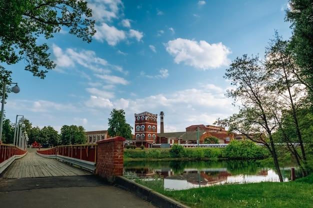 Stadslandschap met een rivier en uitzicht op een oude papierfabriek onder een blauwe lucht met stapelwolken