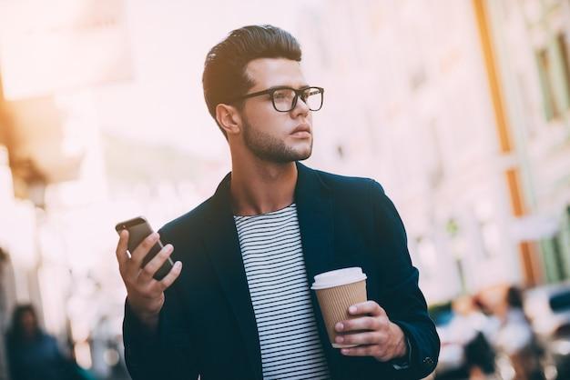 Stadsleven. knappe jonge man in slimme vrijetijdskleding die langs de straat loopt terwijl hij een koffiekopje en een smartphone vasthoudt