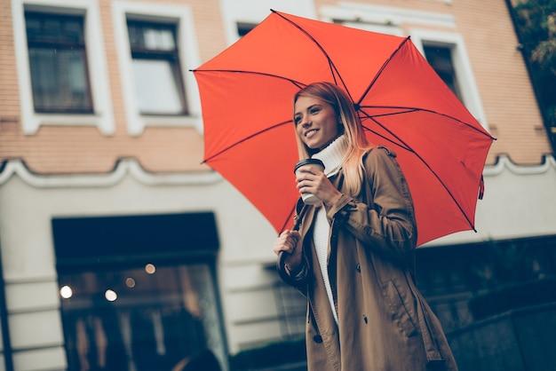 Stadsleven. lage hoekmening van aantrekkelijke jonge glimlachende vrouw die paraplu en koffiekop draagt terwijl ze langs de straat loopt