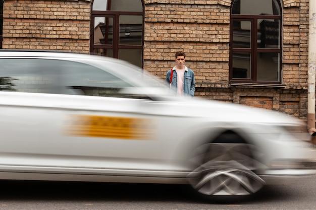 Stadslevensstijl verkeersconcept. knappe jongeman met kapsel in modieuze blauwe spijkerjas staat in de buurt van vintage bakstenen gebouw in de stad. homo in jeanskleding op straat in de buurt van weg met taxiauto