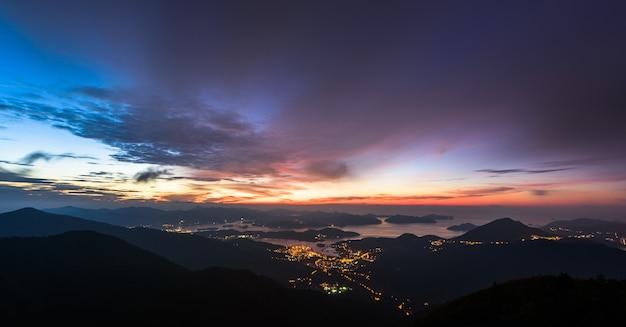 Stadslichten en bergen tijdens zonsondergang