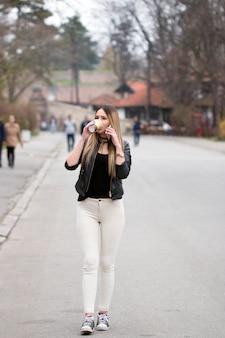 Stadsmeisje met slimme telefoon en koffiekop