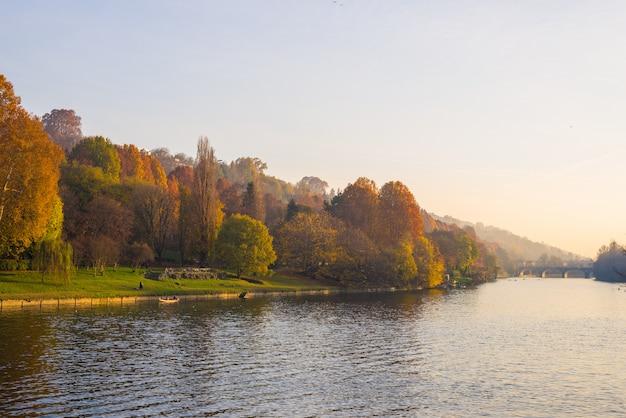 Stadsmening van turijn (turijn - italië) bij zonsondergang in de herfstseizoen met kerk op heuveltop die po-rivier en kleurrijke bomen overzien.
