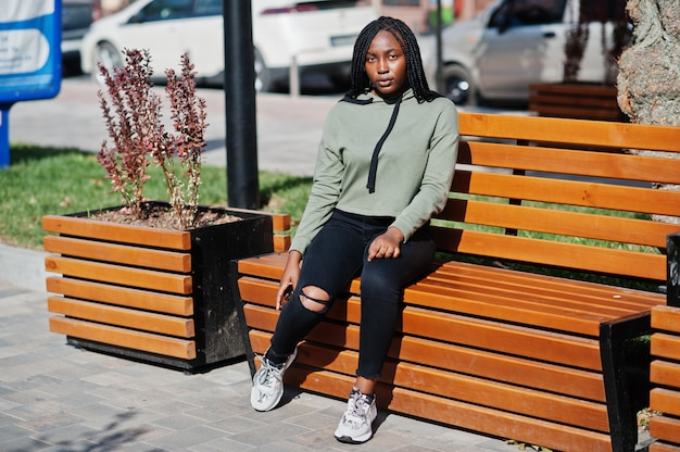 Stadsportret van positief jong donker gevild wijfje dat groene hoody zitting op bank draagt.