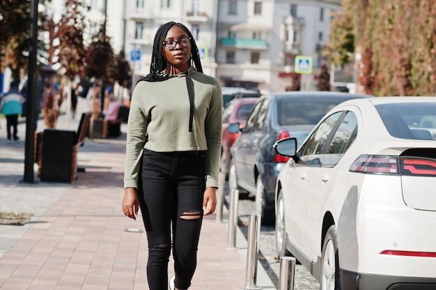 Stadsportret van positief jong donker gevild wijfje groen hoody dragen en oogglazen die bij autoparkeren lopen.
