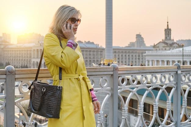 Stadsportret van rijpe glimlachende vrouw in gele laag die op mobiele telefoon spreekt