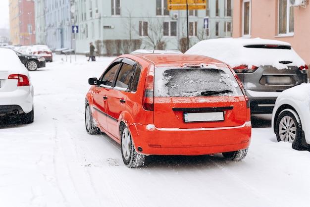Stadsstraat bedekt met sneeuw na sneeuwstorm. geparkeerde auto's in de straat op een sneeuwstorm winterdag. cyclonen concept