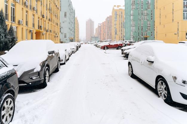 Stadsstraat bedekt met sneeuw na sneeuwstorm. rijen geparkeerde auto's in de straat op een sneeuwstorm winterdag. cyclonen concept
