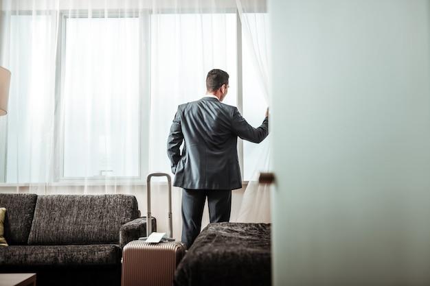 Stadszicht controleren. donkerharige succesvolle zakenman die het uitzicht op de stad controleert vanuit zijn hotelkamer