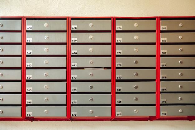 Stalen brievenbussen in een flatgebouw. even rijen genummerde brievenbus. correspondentieconcept in de stad. je kunt het gebruiken als achtergrond voor je advertentie. ruimte kopiëren