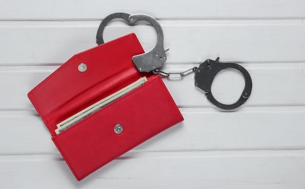 Stalen handboeien met rode lederen portemonnee op witte tafel. diefstal, crimineel concept.