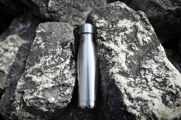 Stalen waterfles in het midden van de rotsen blanco roestvrijstalen dubbelwandige trainingsfles
