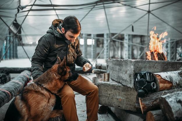 Stalker die een hond voedt, apocalypsconcept. post apocalyptische levensstijl op ruïnes, dag des oordeels, dag des oordeels
