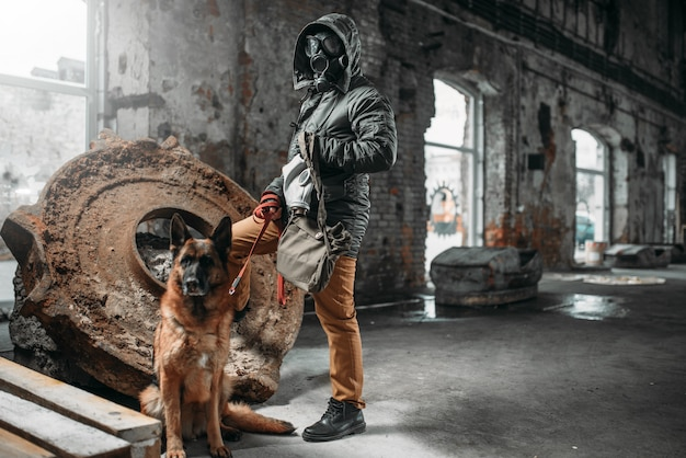 Stalker in gasmasker en hond in puin, overlevenden in gevarenzone na nucleaire oorlog. post apocalyptische wereld. levensstijl na de apocalyps, dag des oordeels, dag des oordeels