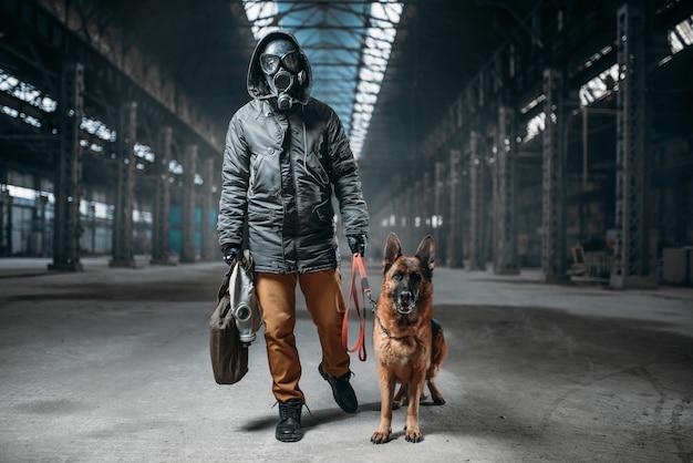 Stalker in gasmasker en huisdier in verlaten gebouw, overlevenden na een kernoorlog. post apocalyptische wereld. post-apocalyps levensstijl op ruïnes, dag des oordeels, dag des oordeels
