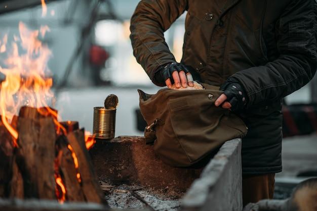 Stalker, mannelijke persoon verwarmt zijn handen in brand