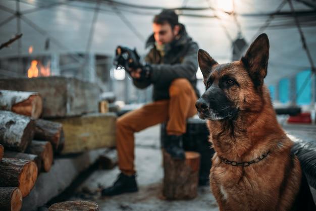 Stalker meet het stralingsniveau in de nucleaire explosiezone tegen zijn hond. post apocalyptische levensstijl op ruïnes, dag des oordeels, dag des oordeels